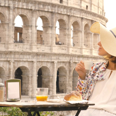 Happy young woman tourist drinking coffee and juice with cornetto at the table outside a bar restaurant in front of the Colosseum in Rome.