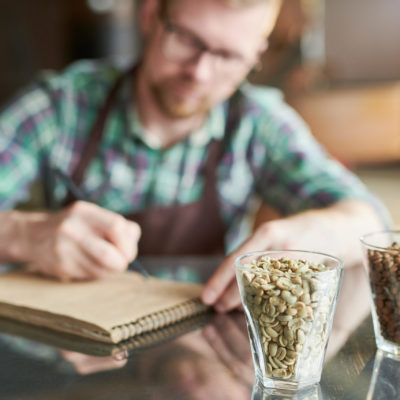 Two glasses of coffee beans, raw and roasted on table in modern roastery with blurred form of barista taking notes in background, copy space