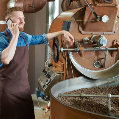 Portrait of handsome modern barista wearing apron speaking by phone while standing at coffee roasting machine in local roastery, copy space