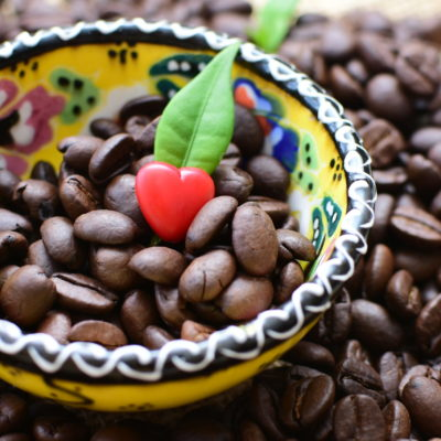 Coffee beans decorated with red heart and green leaves